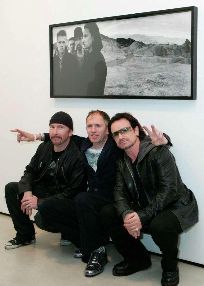 "U2 guitarist the Edge, from left, photographer Anton Corbijn and Bono celebrate the naming of ""The Joshua Tree"" album to the National Recording Registry. Photo: Diane Bondareff, STR / AP"