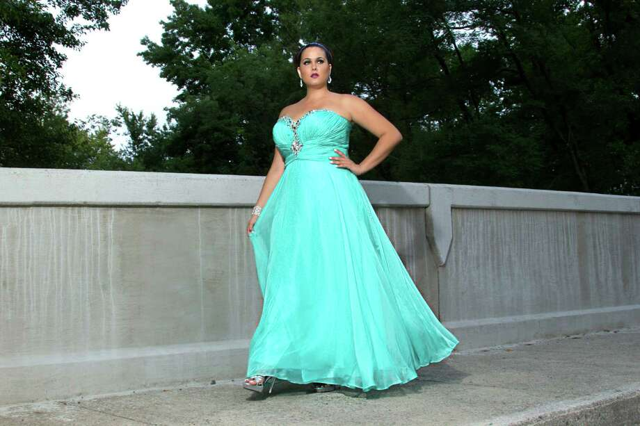 This product image released by Sydney's Closet shows a woman modeling a plus size prom dress. Clothes shopping for plus-size teens can be frustrating in general, but shopping for a dream prom dress can be a tear-inducing, hair-pulling morass of bad design and few options _ especially for girls who want a dress that hugs the body instead of tenting it. Photo: Sydney's Closet, AP / Sydney's Closet