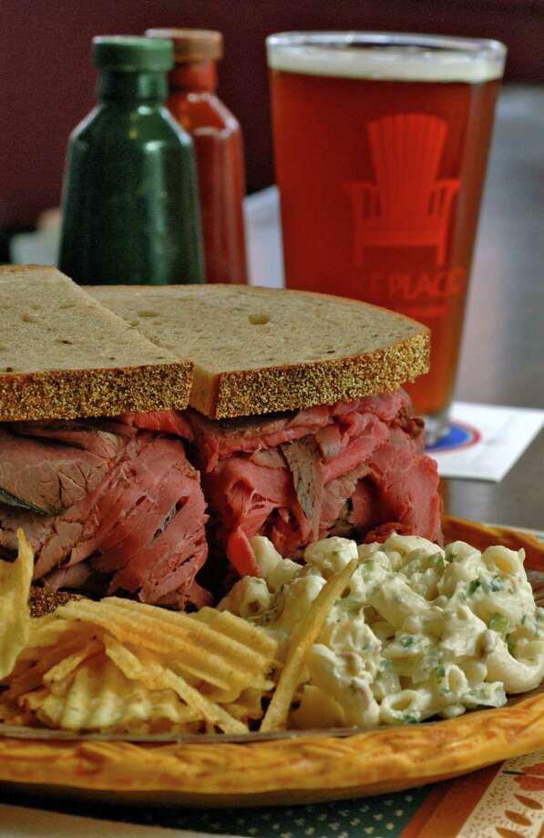 One of Slick's Tavern's signature oversized sandwiches, roast beef, sits on the bar with a pickle, macaroni salad, and a beer. Photo: PHILIP KAMRASS / ALBANY TIMES UNION