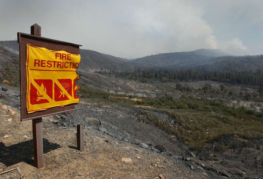 A road sign shows fire damage above a valley scorched by the Rim Fire in Tuolumne County on Saturday, Aug. 24, 2013. Photo: Paul Chinn, The Chronicle