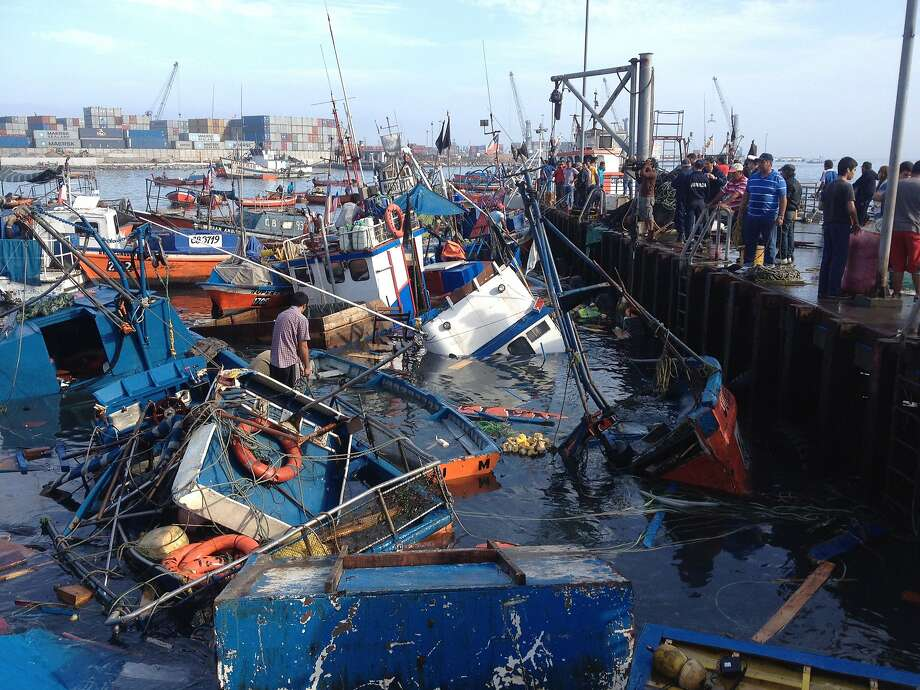 Mangled marina:Capsized fishing boats float in the harbor at Riquelme Cove in Iquique, Chile, after an 