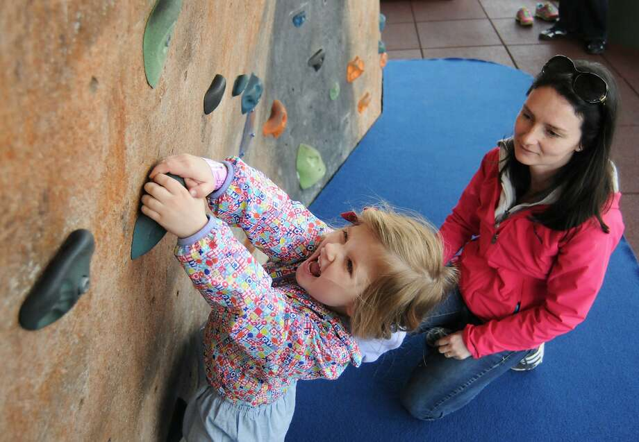 Because it's there: Three-year-old Amelie Kraklau tries to climb a bouldering wall under the 