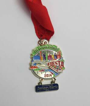 San Antonio Chamber of Commerce's 2014 Fiesta medal will be handed out at various events and features a movable barge on the San Antonio River. Photo: Juanito M. Garza, San Antonio Express-News / San Antonio Express-News