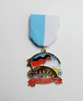 The Royal Order of the Golden Wurst, the Beethoven Maennerchor's whimsical medal features a spinning sausage and celebrates the group's annual Fiesta Gartenfest, April 23-25, and the guys on the food line. Medals are $10, and proceeds will go to the restoration of the group's nine-pin bowling alley. Photo: Juanito M. Garza, San Antonio Express-News / San Antonio Express-News