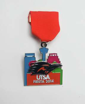 University of Texas at San Antonio Fiesta medal, featuring its twirling Roadrunner mascot, was designed by President Ricardo Romo. It's available at the Fiesta Store and at the Roadrunner Express on the Main Campus. Photo: Juanito M. Garza, San Antonio Express-News / San Antonio Express-News