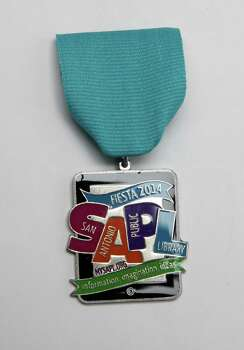 "The San Antonio Public Library's 2014 Fiesta medal celebrates ""information, imagination, ideas,"" $6, at the Fiesta Store. Photo: Juanito M. Garza, San Antonio Express-News / San Antonio Express-News"