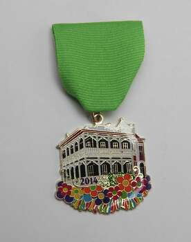 The Molina Manor Porch Party Fiesta Medal is given by Belinda Valera Molina to her guests at her sixth-annual King William Parade-watching party. Her home is the old Stieren House, built in 1891 by C.A. Stieren. Photo: Juanito M. Garza, San Antonio Express-News / San Antonio Express-News
