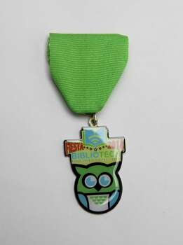 Bexar County Digital Library BiblioTech's first Fiesta medal shows off its mascot, Techolote, or owl. It's not for sale but can be earned by coming to the library, 3505 Pleasanton Road, and answering a trivia question about Bexar County or San Antonio using the library's resources. That starts April 10 until supplies last. Added value: Download the BiblioTech's augmented reality app — BexarCountyAR — on  a device running on Apple iOS or the latest version of Android software (2.2 or later), point at a Techolote medal and the owl will come to life. He'll blink his eyes, do a Fiesta dance and bring up links to the digital library's collection search, social media channels and registration link. Photo: Juanito M. Garza, San Antonio Express-News / San Antonio Express-News