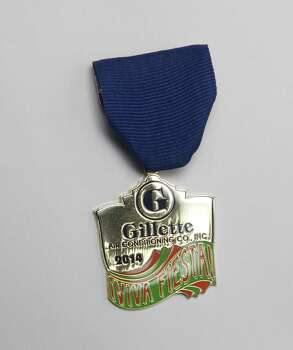 "Gillette Air Conditioning, Inc., first Fiesta medal comes on the company's 55th anniversary, and was made by two long-time employees Judy and Dean Bowen. ""We will be retiring soon, and we thought this would be a nice keepsake for the Gillettees to distribute to employees, friends, relatives and customers,"" writes Judy Bowen. ""The Gillettees have been like family to us, and we appreciate all that they have done for us over the years."" Photo: Juanito M. Garza, San Antonio Express-News / San Antonio Express-News"