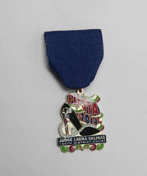 Judge Laura Salinas of the 166th District Court is celebrating Fiesta with this medal, featuring the scales of justice, a high-heeled shoe and a string of pearls. She'll be out during Fiesta and giving them away. Photo: Juanito M. Garza, San Antonio Express-News / San Antonio Express-News