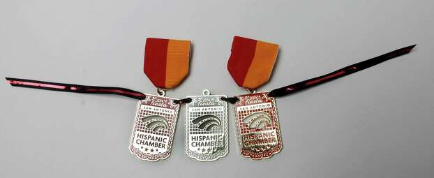 San Antonio Hispanic Chamber of Commerce 2014 Fiesta Medals in red, silver and orange will be sold for $10 each at the Pin Pandemonium and at chamber offices at The Pearl, but members of the chamber's staff also will give them away at Fiesta events. Designed as papel picado, they can be strung together with ribbon. Photo: Juanito M. Garza, San Antonio Express-News / San Antonio Express-News