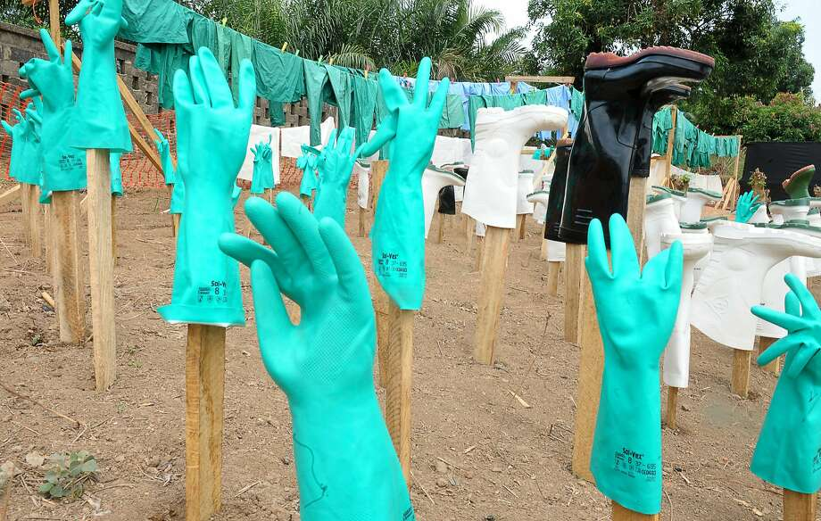 Ebola outbreak:Gloves and boots used by medical staff dry in the sun at a center for victims of the Ebola   virus in Guekedou, Guinea. The viral hemorrhagic fever epidemic raging in Guinea is caused   by several viruses that have similar symptoms, of which the deadliest and most feared is   Ebola. Photo: Seyllou, AFP/Getty Images