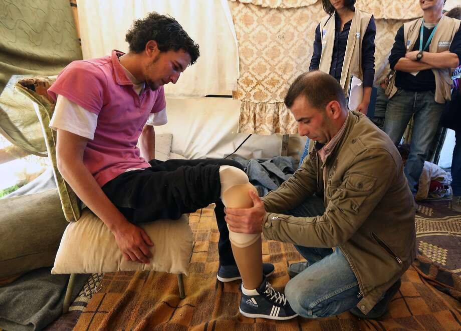 In this Thursday, March. 27, 2014 photo, Mustafa Ahmad, left, a 19-year-old who lost his leg in his hometown of Deir Hafer in Aleppo province in November 2011 when government warplanes bombed his neighborhood, is fitted with a prosthetic leg by a Lebanese prosthetic limb maker, right, at the Syrian refugee camp in Jib Janine, in the Bekaa valley, Lebanon. Syria's civil war, which entered its fourth year last month, has killed more than 150,000 people. An often overlooked figure is the number of wounded more than 500,000, according to the International Committee of the Red Cross. An untold number of those, there's no reliable estimate even, have suffered traumatic injuries that have left them physically handicapped. (AP Photo/Bilal Hussein) Photo: Bilal Hussein, Associated Press