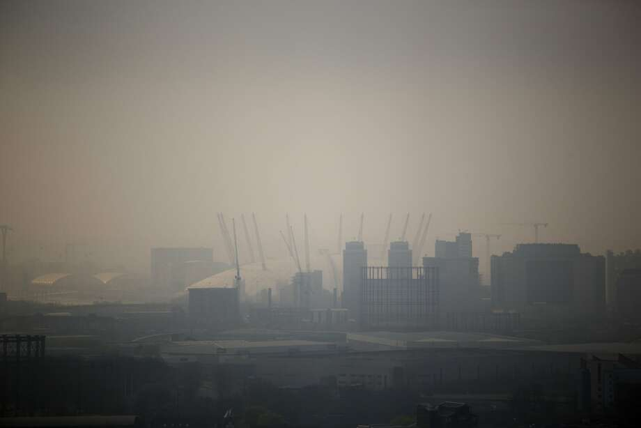 The Millennium Dome is shrouded in smog in London, as seen from a viewing gallery in the Orbit sculpture during a tour organized for the media, Wednesday, April 2, 2014. British authorities have warned people with heart or lung conditions to avoid exertion as a combination of industrial pollution and Sahara dust blankets the country in smog. The environment department said Wednesday's air pollution level could reach the top rung on its 10-point scale.  (AP Photo/Matt Dunham) Photo: Matt Dunham, Associated Press