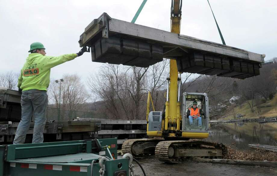 Blaze Martin, left, M&O Construction and Dwayne Action of FirstLight Power Resouces, and Ronny Steeves, right, guide a dock onto a truck, Wednesday, April 2, 2014, at The Marina in New Fairfield, Conn.  FirstLight has evicted the owner of The Marina. Photo: Carol Kaliff / The News-Times