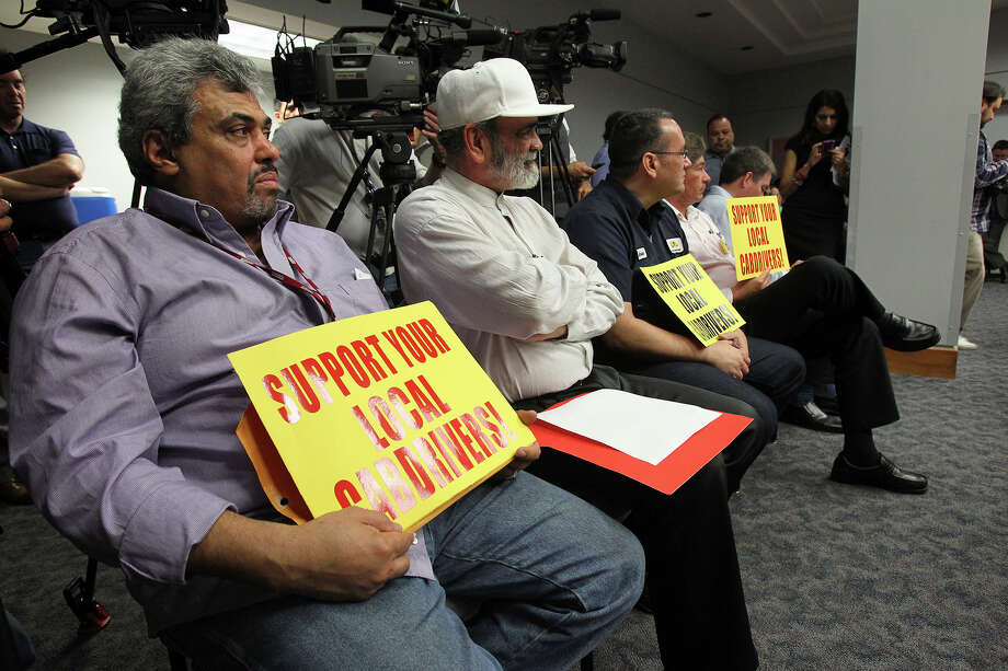 Cab drivers hold signs as citizens express their views about the new transportation organization competing in San Antonio during a session at City Hall  on April 2, 2014. Photo: TOM REEL