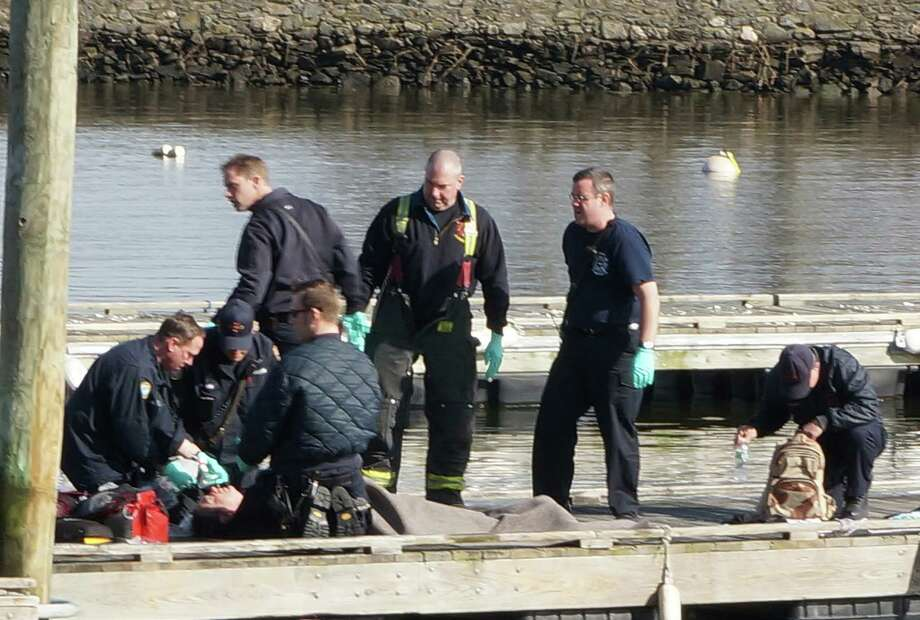 Emergency personnel treat a kayaker who capsized Wednesday afternoon and fell into the water near the mouth of Southport Harbor. The kayaker, who was wearing a life vest, had no identification on him. Photo: Genevieve Reilly / Fairfield Citizen