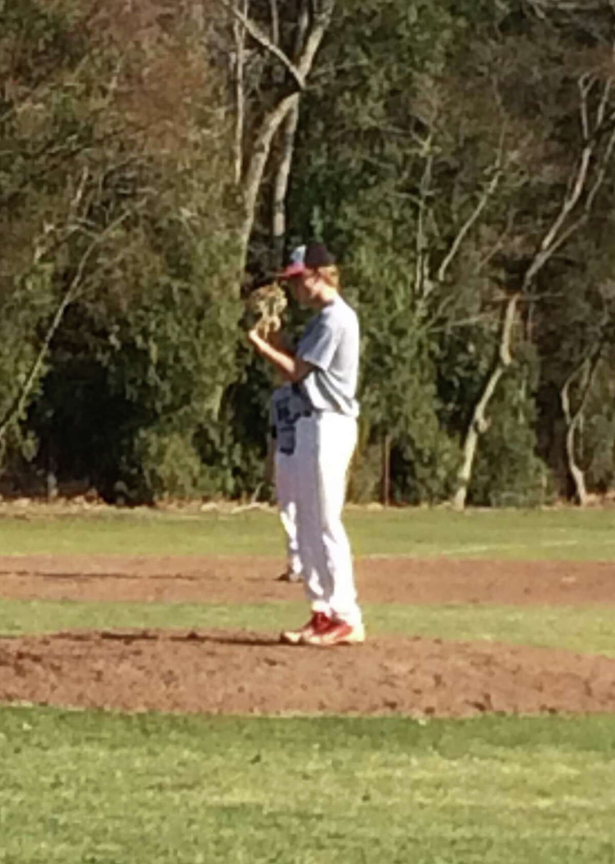 New Canaan's J.R. Anderson prepares to deliver a pitch in the early innings of his team's home scrimmage against Stamford at Mead Park on Wednesday, April 2.