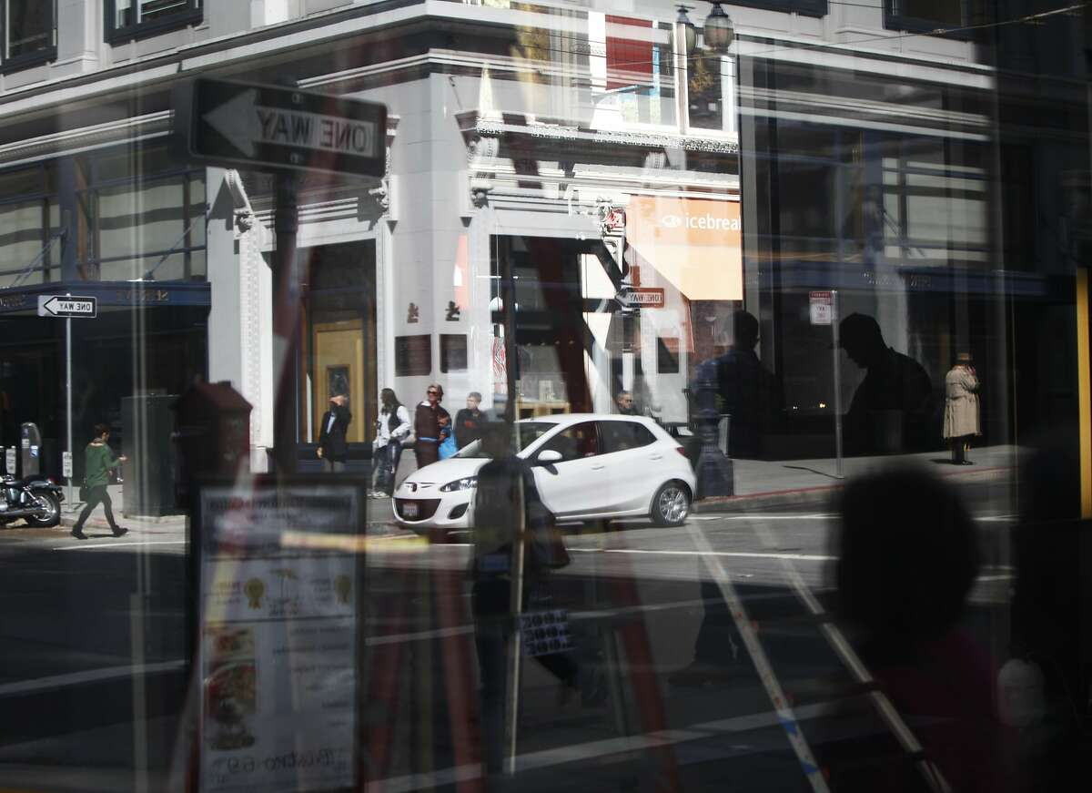 Cars and pedestrians are seen crossing the intersection of Grant and Post in a reflection on April 2, 2014 in San Francisco, Calif. A new study has found that San Francisco is the second most dense area in the U.S.