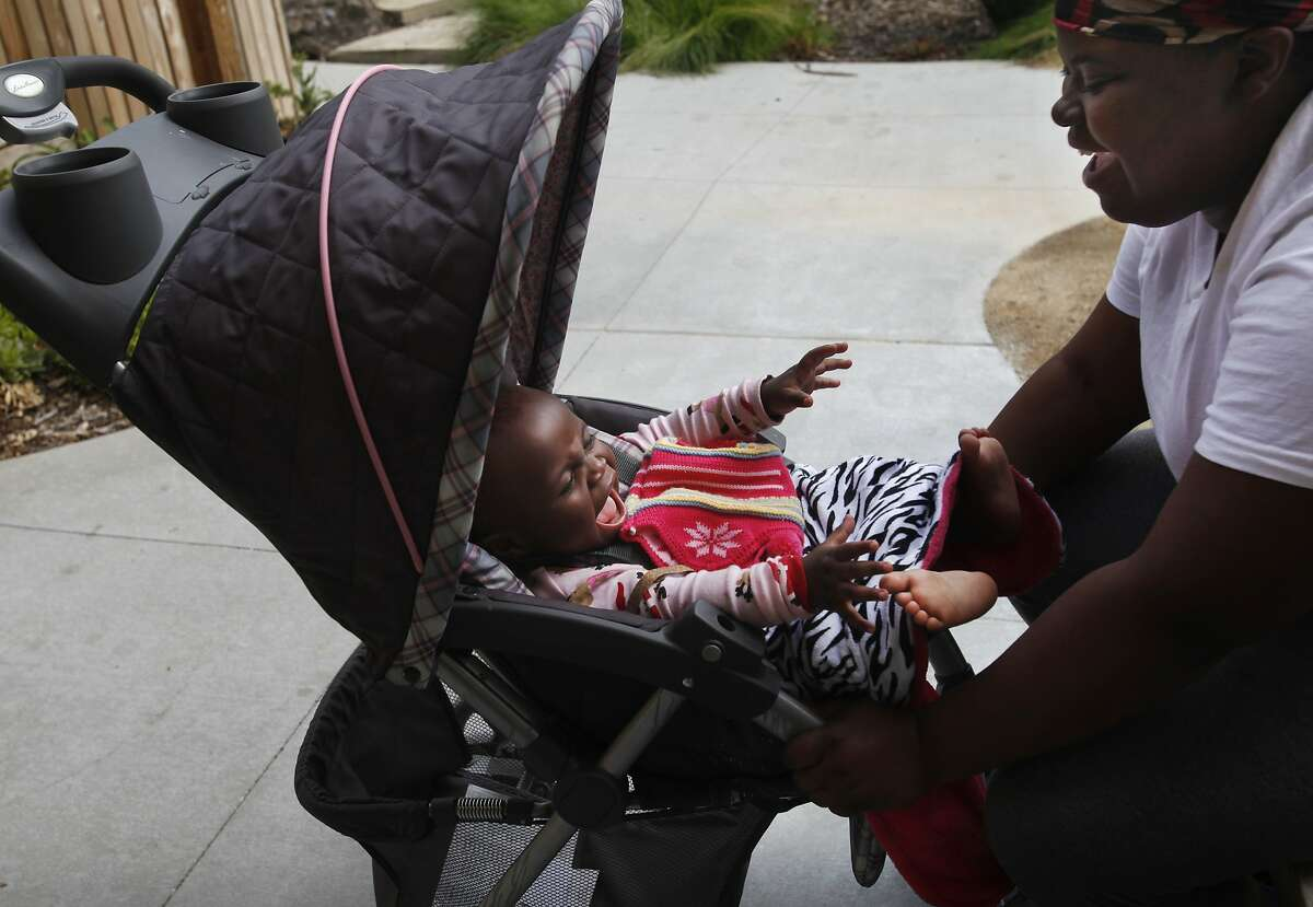 Robin Gilchrist, 20, right, plays with her daughter, Aaniyah Nash, 1, in the courtyard outside of her apartment March 28, 2014 at Rising Oaks apartment complex on the Fred Finch Youth Center campus in Oakland, Calif. The 30-unit housing, which opened last June, provides transitional subsidized housing for low-income, former or current foster youth as well as youth on probation. Gilchrist spent most of her life in the foster system. She has been at Rising Oaks since November, she says it has been a blessing for her. She doesn't want to put her daughter into daycare until she's old enough to speak so that she can tell Gilchrist if something is wrong, or if someone is mistreating her.