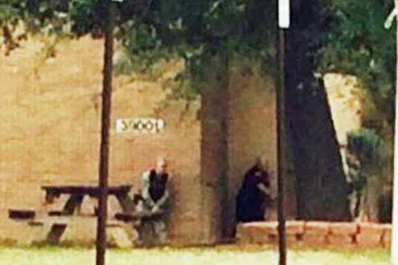 Law enforcement officials with guns drawn approach a building at Ft. Hood where a shooting was reported Wednesday late afternoon. Bell County Sheriff's Office also reported a shooting on the post.