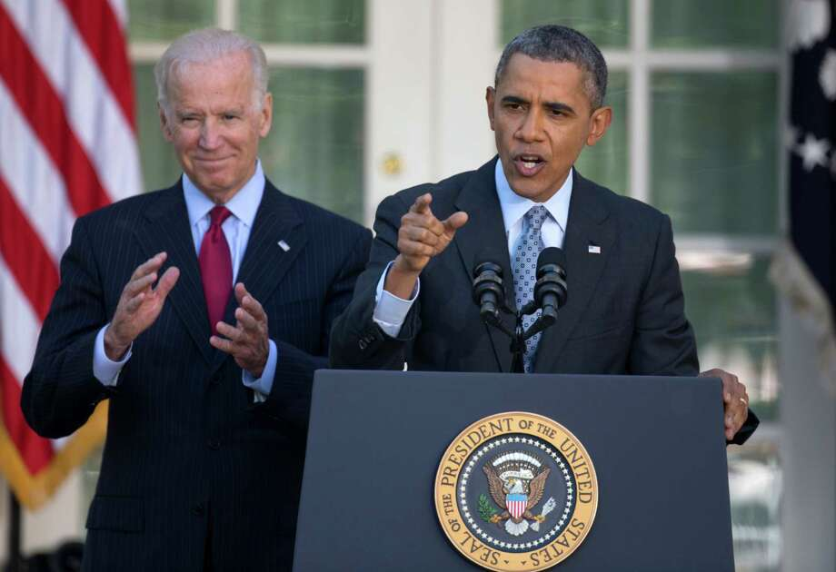 President Barack Obama, with Vice President Joe Biden, gestures as he speaks in the Rose Garden of the White House in Washington, Tuesday, April 1, 2014, about the Affordable Care Act. The deadline to sign up for health insurance under the Affordable Care Act passed at midnight Monday night. (AP Photo/Carolyn Kaster) Photo: Carolyn Kaster, STF / AP