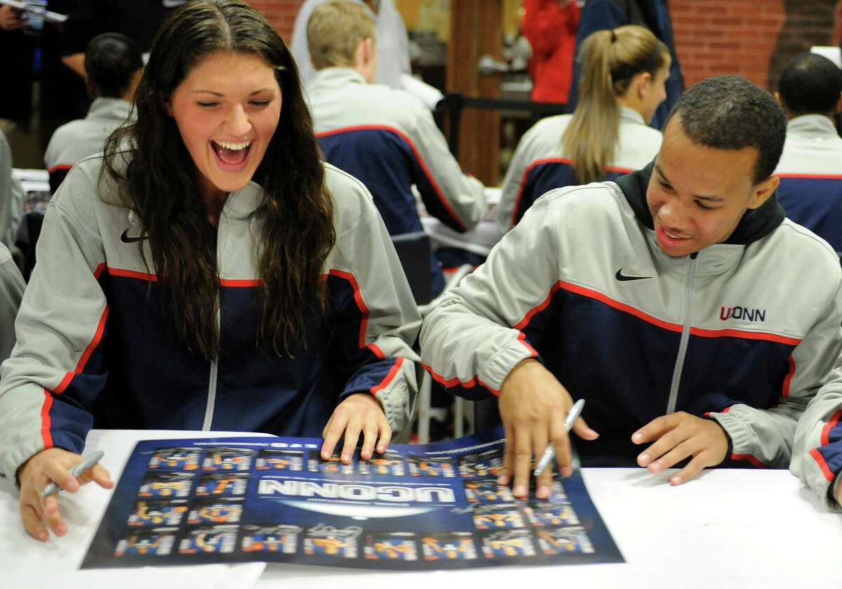 Connecticut's Stefanie Dolson, left, and Shabazz Napier laugh while signing autographs during the men's and women's basketball's First Night festivities in Storrs, Conn., Friday, Oct. 12, 2012. (AP Photo/Jessica Hill)