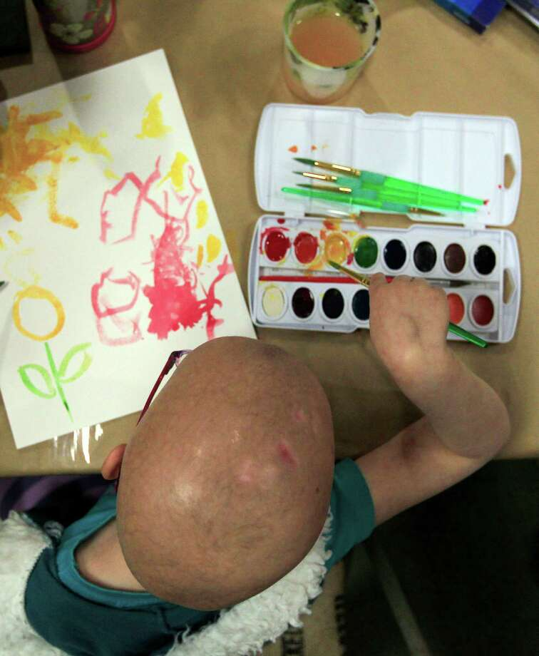 Hannah Meeson, 6, who is undergoing treatment for brain cancer, picks a color as a group of young cancer patients from The University of Texas MD Anderson Cancer Center Children's Art Project painted and drew art inspired by plants and flowers at Cornelius Nursery. Photo: Johnny Hanson, Houston Chronicle / © 2014  Houston Chronicle