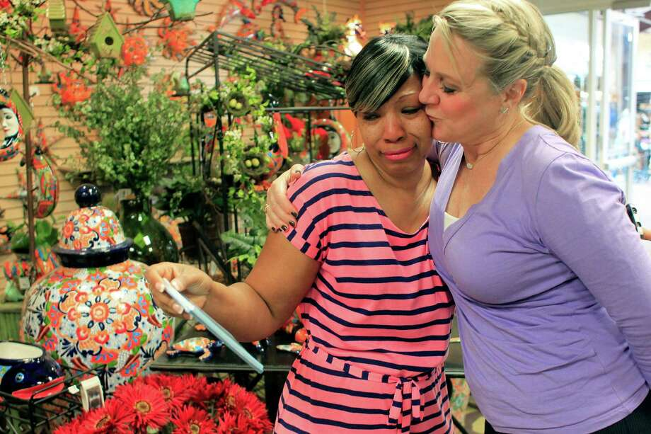 """Shannan Murray, right, executive director of the MD Anderson Cancer Center Children's Art Project, gives Marla Jones a hug and a kiss as she looked at the art work her daughter Khyrstin """"Kyssi"""" Andrews, 5, created that is now on cards at Cornelius Nursery. Photo: Johnny Hanson, Houston Chronicle / © 2014  Houston Chronicle"""