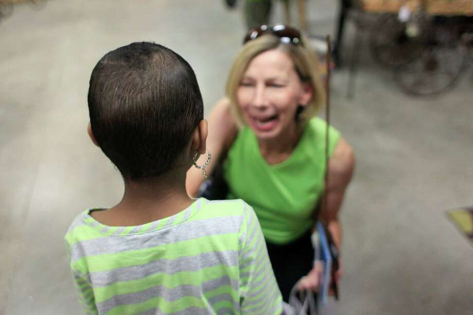 """""""I want your autograph,"""" Marsha Horton said to five-year-old Khyrstin """"Kyssi"""" Andrews, 5, as she purchased as a package of cards created by Andrews. Photo: Johnny Hanson, Houston Chronicle / © 2014  Houston Chronicle"""