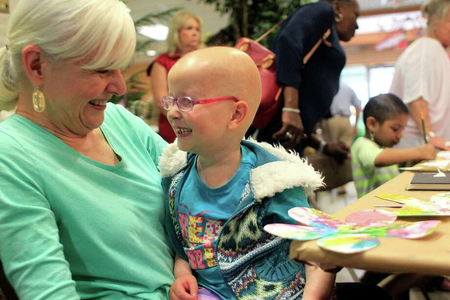 Volunteer Celia Anderson shares a smile after working with Hannah Meeson, 6, who is undergoing treatment for brain cancer, as a group of young cancer patients from The University of Texas MD Anderson Cancer Center Children's Art Project painted and drew art inspired by plants and flowers at Cornelius Nursery. Photo: Johnny Hanson, Houston Chronicle / © 2014  Houston Chronicle