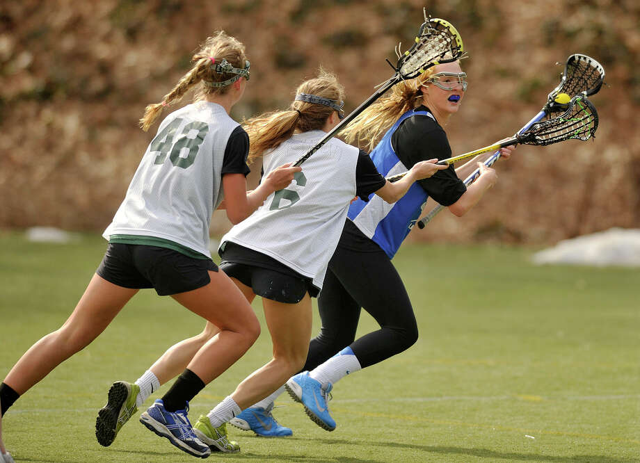 Darien's Hollis Perticone, right, is double-teamed by Greenwich Academy's Izzy Nixon, left, and Izzy Viola during their scrimmage at Greenwich Academy in Greenwich, Conn., on Wednesday, April 2, 2014. Darien won, 14-6. Photo: Jason Rearick / Stamford Advocate