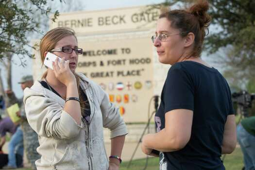 Krystina Cassidy and Dianna Simpson attempt to make contact with their husbands who are stationed inside Fort Hood, while standing outside of the Bernie Beck Gate, on Wednesday, April 2, 2014, in Fort Hood, Texas. One person was killed and 14 injured in a shooting Wednesday at Fort Hood, and officials at the base said the shooter is believed to be dead. Photo: Tamir Kalifa, Associated Press / AP2014