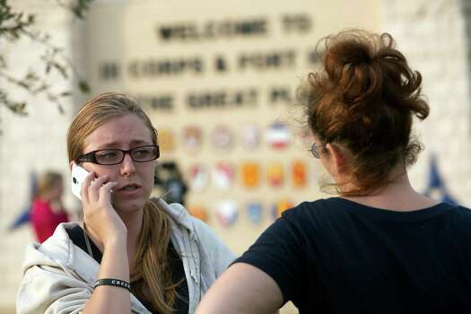 Krystina Cassidy, left, and Dianna Simpson attempt to make contact with their husbands who are stationed inside Fort Hood while standing outside of the Bernie Beck Gate on Wednesday, April 2, 2014, in Fort Hood, Texas. At least one person was killed and 14 injured in the shooting, and officials at the base said the shooter is believed to be dead. (AP Photo/ Tamir Kalifa) Photo: Tamir Kalifa, Associated Press / FR170773 AP