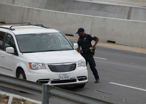 A police officer checks drivers' IDs outside the main gate at Fort Hood, Texas, after a shooting at the Army base Wednesday, April 2, 2014.  One person was killed and at least 14 injured in a shooting Wednesday at Fort Hood. (AP Photo/Austin American-Statesman, Deborah Cannon)  AUSTIN CHRONICLE OUT, COMMUNITY IMPACT OUT, MAGS OUT; NO SALES; INTERNET AND TV MUST CREDIT PHOTOGRAPHER AND STATESMAN.COM Photo: Deborah Cannon, Associated Press / Austin American-Statesman
