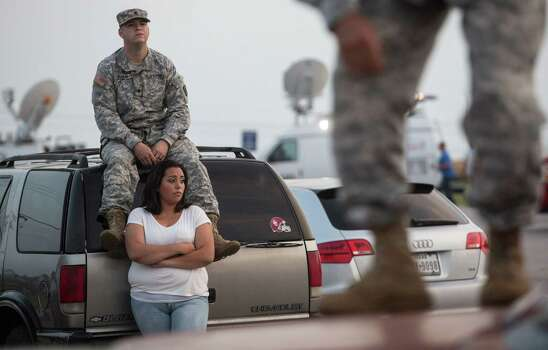 Lucy Hamlin and her husband, Spc. Timothy Hamlin, wait for permission to re-enter the Fort Hood military base, where they live, following a shooting on base on Wednesday, April 2, 2014, in Fort Hood, Texas. One person was killed and 14 injured in the shooting, and officials at the base said the shooter is believed to be dead. The details about the number of people hurt came from two U.S. officials who spoke on condition of anonymity because they were not authorized to discuss the information by name. (AP Photo/ Tamir Kalifa) Photo: Tamir Kalifa, Associated Press / FR170773 AP