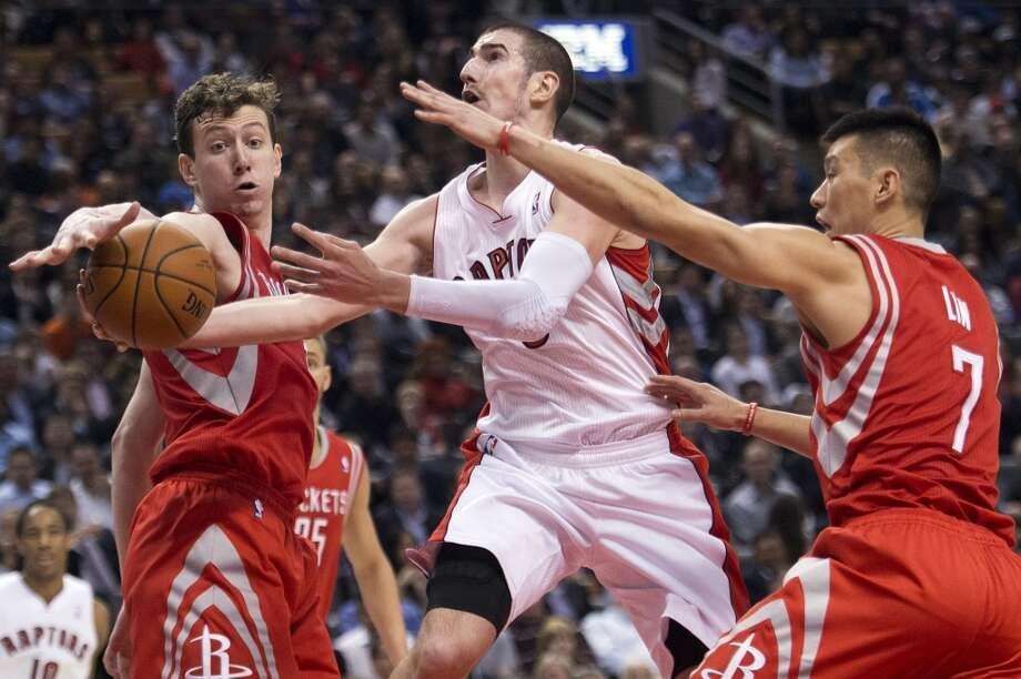Omer Asik and Jeremy Lin of the Rockets defend Nando de Colo of the Raptors. Photo: Nathan Denette, The Associated Press/The Canadian Press