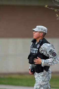 A Military Police officer runs toward the road leading to the Main Gate, Wednesday, April 2, 2014, as an active shooter remains at large at Fort Hood, Texas. Three people were killed and 14 injured in the shooting, and officials at the base said the shooter is believed to be dead. The details about the number of people hurt came from two U.S. officials who spoke on condition of anonymity because they were not authorized to discuss the information by name. Photo: Rusty Schramm, Associated Press / The Temple Daily Telegram