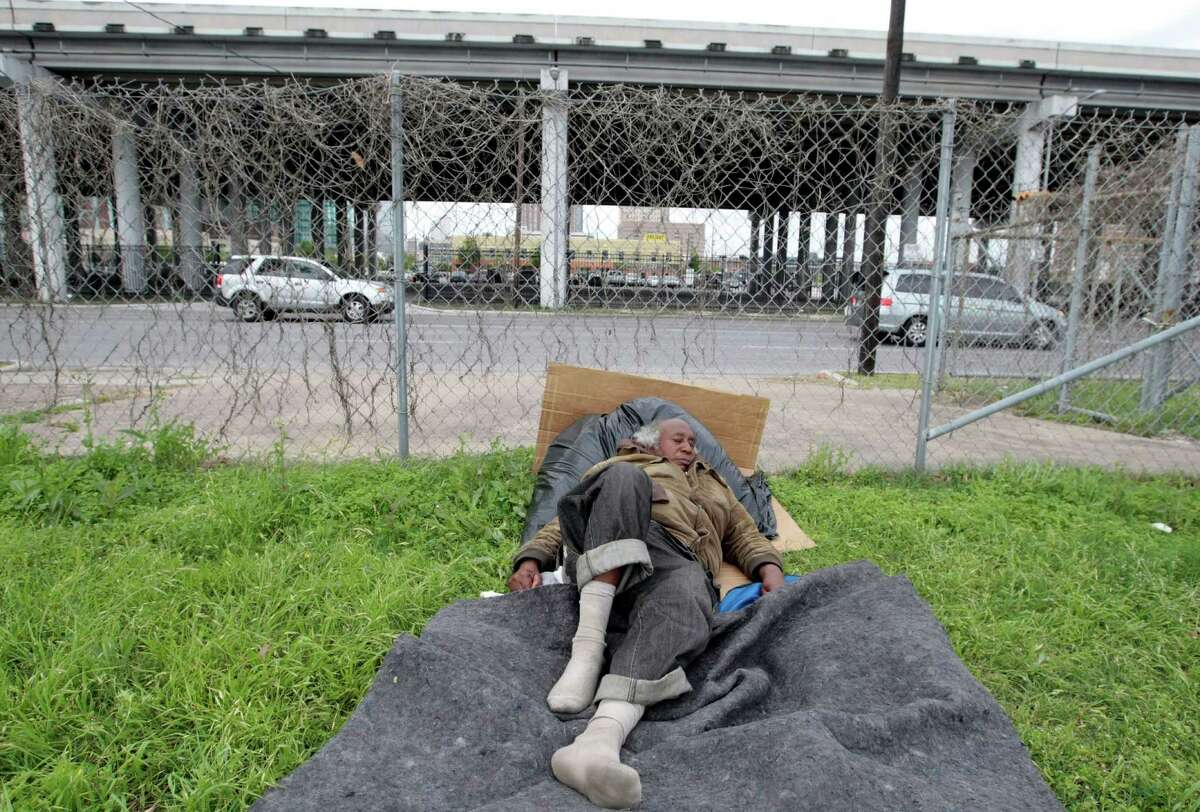 Seventy year-old Lionel Ross lays in a vacant lot at Chartres St. and Franklin St. in downtown Houston, TX Wednesday April 2, 2014. Ross a Houston native has says he's been homeless for thirty years. Efforts to reduce Houston's chronic homeless population have cut the number of long-term downtown street-dwellers nearly in half since 2012, Mayor Annise Parker announced Wednesday.(Billy Smith II / Houston Chronicle)