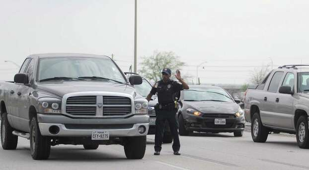 Emergency personnel caution drivers away from the Bernie Beck Main Gate following reports of a shooting, Wednesday, April 2, 2014 at Fort Hood, Texas. (AP Photo/Killeen Daily Herald, Catrina Rawson) MANDATORY CREDIT NO SALES Photo: Catrina Rawson, Associated Press / Killeen Daily Herald