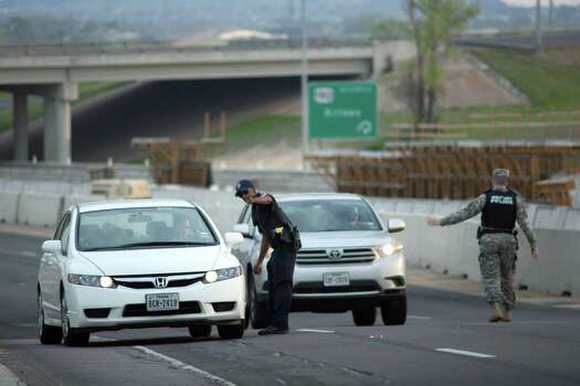 Local and Military police direct traffic outside of an entrance to Fort Hood following reports of an active shooting on the military base in Wednesday, April 2, 2014, in Fort Hood, Texas. (AP Photo/Tamir Kalifa) Photo: Tamir Kalifa, Associated Press / FR170773 AP