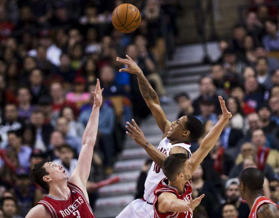 DeMar DeRozan of the Raptors attempts a shot against Rockets center Omer Asik. Photo: Nathan Denette, The Associated Press/The Canadian Press