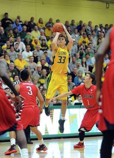 Siena's Rob Poole puts up a three point shot during game two of the College Basketball Invitational
