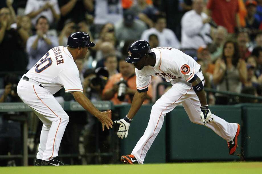 Third-base coach Pat Lisatch (left) congratulates Astros center fielder Dexter Fowler after his first-inning home run. Fowler also hit a triple. Photo: Karen Warren / Houston Chronicle / © 2014 Houston Chronicle