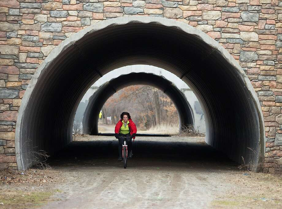 Jean LaSala of Tolland Conn.,  passes underneath Interstate 84 while out for her first bike ride of the season on the Vernon Conn. Rails to Trails on Wednesday April 2, 2014. Spring weather has arrived with temperatures in the mid-fifties to sixties forecasted for the week. (AP Photo/Journal Inquirer, Jared Ramsdell) Photo: Jared Ramsdell, Associated Press
