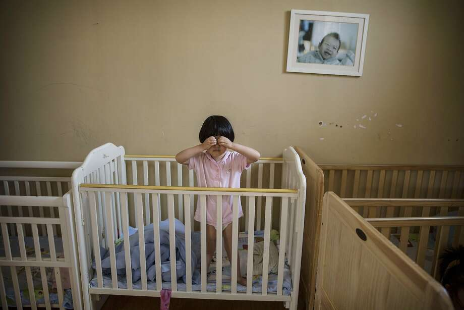 An orphaned Chinese girlstands in a crib at a foster-care center in Beijing. China's orphanages and foster homes used to be filled with healthy girls, reflecting the country's one-child policy and its 