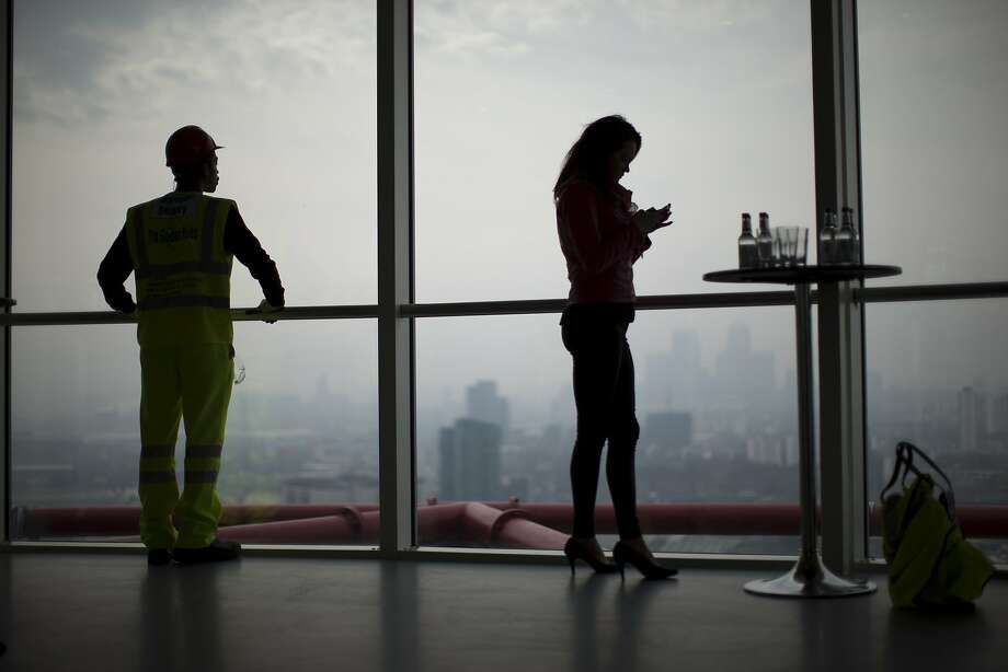 Two apprentices who work on the Queen Elizabeth Olympic Park and were on hand for members of the media to interview, wait by the windows of a viewing gallery in the Orbit sculpture as London's Canary Wharf business district and other parts of the capital stand shrouded in smog in the background during an Olympic Park tour organized for the media, Wednesday, April 2, 2014.  British authorities have warned people with heart or lung conditions to avoid exertion as a combination of industrial pollution and Sahara dust blankets the country in smog.  The environment department said Wednesday's air pollution level could reach the top rung on its 10-point scale.  (AP Photo/Matt Dunham) Photo: Matt Dunham, Associated Press