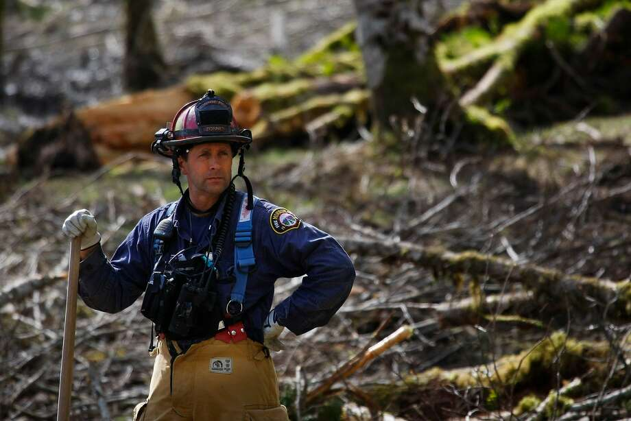 Capt. Jeff Zonrnes, of the Monroe Fire Department, looks on in the debris field, Wednesday, April 2, 2014, as volunteers worked to clear more of the mudslide area in Oso, Wash. A deadly mudslide in March killed more than two dozen people. (AP Photo/The Herald, Genna Martin) Photo: Genna Martin, Associated Press