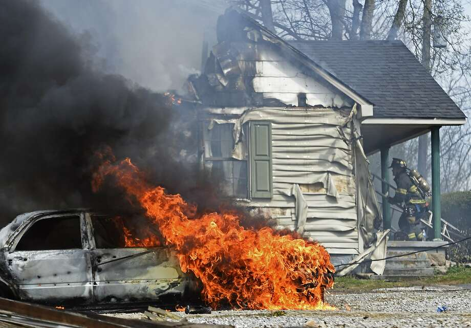 A firefighter battles a  house fire that spread to adjacent car in south Knoxville, 