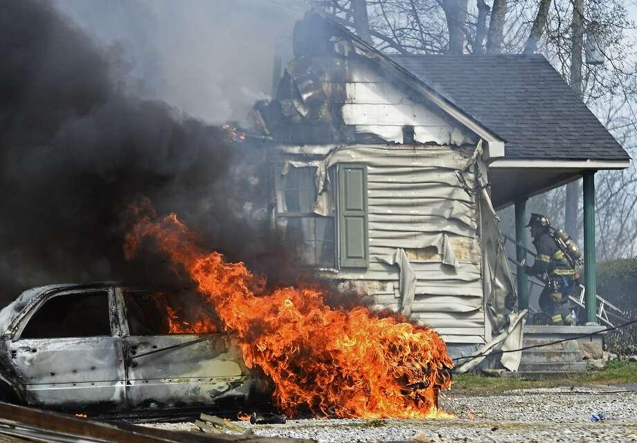 A firefighter battlesa  house fire that spread to adjacent car in south Knoxville,   Tenn. Photo: Adam Lau, Associated Press